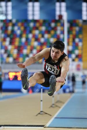 salto de longitud: ESTAMBUL, Turquía - 14 de febrero 2015: El atleta Alper Yuksel salto de longitud durante Turkcell Juniors y Seniors Atletismo Turquía Campeonato de interior en el pabellón Asli Cakir Alptekin Atletismo