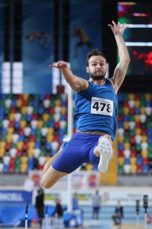 salto de longitud: ESTAMBUL, Turquía - 14 de febrero 2015: El atleta Ali Sari salto de longitud durante Turkcell Juniors y Seniors Atletismo Turquía Campeonato de interior en el pabellón Asli Cakir Alptekin Atletismo