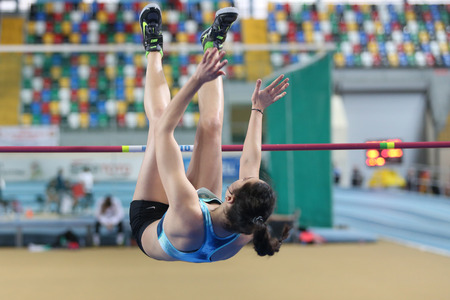 ISTANBUL, TURKEY - FEBRUARY 15, 2015: Athlete Esengul Gokdemir high jump during Turkcell Juniors and Seniors Athletics Turkey Indoor Championship in Asli Cakir Alptekin Athletics hall Editorial