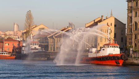 squirt: A fireboat is squirt water in port Editorial