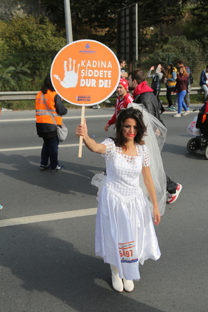 koprusu: ISTANBUL, TURKEY - NOVEMBER 15, 2015: Girl with banner stop to violence against women during 37th Istanbul Marathon. Editorial