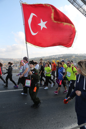 ISTANBUL, TURKEY - NOVEMBER 15, 2015: Man with flag in 37th Istanbul Marathon. More than 100000 people attended to marathon, 15K, 10K and fun run.