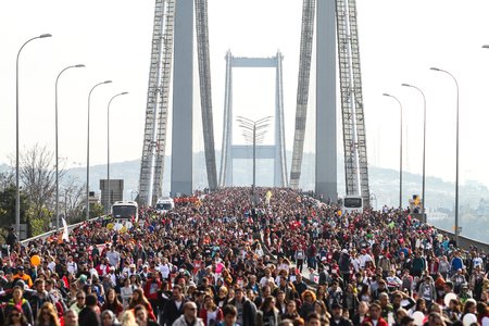 ISTANBUL, TURKEY - NOVEMBER 15, 2015: People are crossing the Bosphorus Bridge from Asia to Europe during 37th Istanbul Marathon. More than 100000 people attended to marathon, 15K, 10K and fun run.