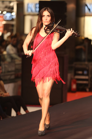 violinist: ISTANBUL, TURKEY - NOVEMBER 07, 2015: Violinist Giselle Tavilson performs during Optimum Fashion days catwalk
