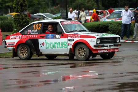 escort: KOCAELI, TURKEY - AUGUST 23, 2015: Burak Turkkan with Ford Escort MK2 of Bonus Unifree Parkur Racing Team in Podium Ceremony of Kocaeli Rally 2015