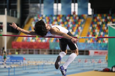 threshold: ISTANBUL, TURKEY - DECEMBER 12, 2015: Athlete Fatih Koca high jumpes during Turkish Athletic Federation Olympic Threshold Indoor Competitions Editorial