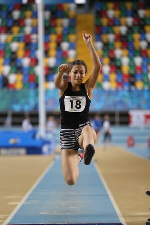 olympic game: ISTANBUL, TURKEY - DECEMBER 12, 2015: Athlete Esra Findik long jumpes during Turkish Athletic Federation Olympic Threshold Indoor Competitions