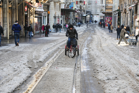 beyoglu: ISTANBUL, TURKEY - JANUARY 01, 2016: Istiklal Avenue in  Beyoglu covered with first snow of season. Istiklal Avenue is the most popular destination of Istanbul for shopping and entertainment.