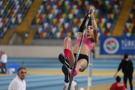 vaulting: ISTANBUL, TURKEY - DECEMBER 26, 2015: Athlete Buse Arikazan pole vaulting during Turkish Athletic Federation Indoor Athletics Record Attempt Races