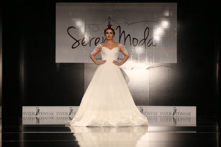 contender: ISTANBUL, TURKEY - JANUARY 31, 2016: Fashion program contender Emel Ozkiziltas showcases one of the latest creations of Seren Moda during Weeding Fair.