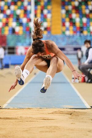 olympic game: ISTANBUL, TURKEY - FEBRUARY 20, 2016: Athlete Tugba Aydin triple jumps during Turkcell Turkish Indoor Athletics Championships Editorial