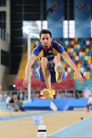 cristian: ISTANBUL, TURKEY - FEBRUARY 25, 2016: Athlete Staicu Cristian Iulian long jumping in Athletics Istanbul Indoor Championships