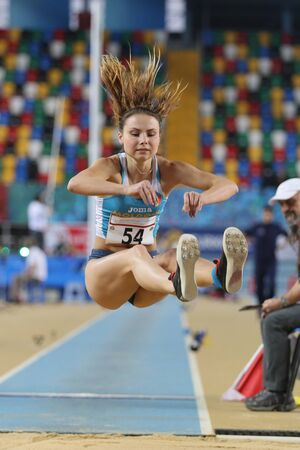 olympic game: ISTANBUL, TURKEY - FEBRUARY 27, 2016: Athlete Uliana Busila long jumping in Balkan Athletics Indoor Championships