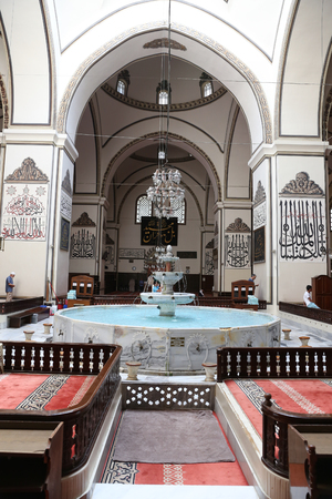 cami: BURSA, TURKEY - JULY 23, 2016: Fountain inside Grand Mosque of Bursa. Mosque was built in 1399 and has 20 domes, 2 minarets. Editorial