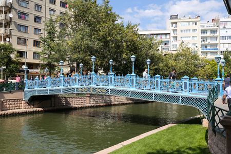 passing over: ESKISEHIR, TURKEY - SEPTEMBER 03, 2016: People passing over the bridge on Porsuk River. Porsuk river is one of the most populer touristy place with boat tours and entertainment in Eskisehir.