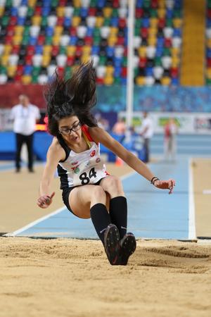 saltar: ISTANBUL, TURKEY - FEBRUARY 12, 2017: Athlete Esra Yilmaz triple jumping during Balkan Junior Indoor Championships Editorial