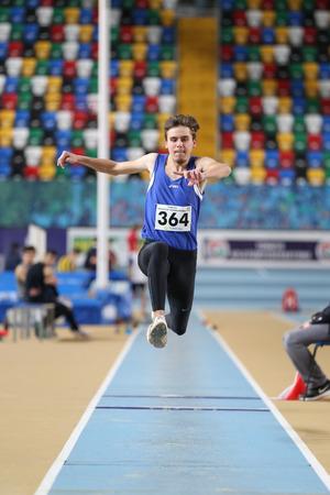 ESTAMBUL, TURQUÍA - 15 DE ENERO DE 2017: Salto triple de Kubilay Kaya del atleta durante carreras interiores del intento del récord del atletismo de la federación atlética turca
