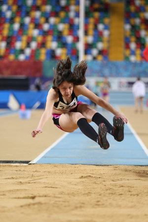 saltar: ESTAMBUL, TURQUÍA - 4 DE FEBRERO DE 2017: Salto triple de Almina Malkoc del atleta durante campeonatos interiores de la juventud turca de Turkcell