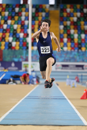 ISTANBUL, TURKEY - FEBRUARY 05, 2017: Athlete Batuhan Cakir triple jumping during Turkcell Turkish Youth Indoor Championships