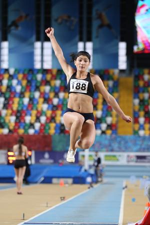 saltar: ISTANBUL, TURKEY - FEBRUARY 05, 2017: Athlete Ecem Calagan long jumping during Turkcell Turkish Youth Indoor Championships