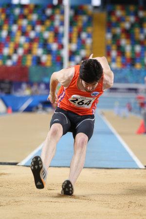 saltar: ISTANBUL, TURKEY - FEBRUARY 05, 2017: Athlete Ramazan Senkal triple jumping during Turkcell Turkish Youth Indoor Championships Editorial