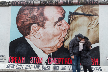 BERLIN, GERMANY - DECEMBER 16, 2017: Couple kissing in front of famous Berlin Wall mural, My God, Help Me to Survive This Deadly Love