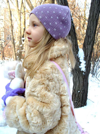 modern doll: Girl in a warm fur clothing. Winter morning. The little girl in profile. A child in a fur coat. Stock Photo