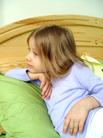 Portrait of a little girl in profile. The little girl sitting on the bed, Young girl sitting on a bed, little sad crying girl sitting on the bed.  Stock Photo - 5900418