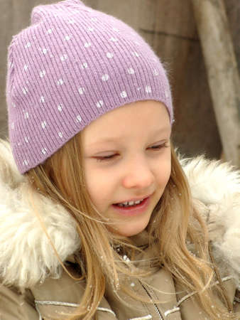 mixed race: Happy little girl in a lilac hat. Winter portrait. A child in winter clothes. A child in a warm winter outerwear. The joy of a child in a winters day. The joy of a child in a winters day, facial expression. Stock Photo