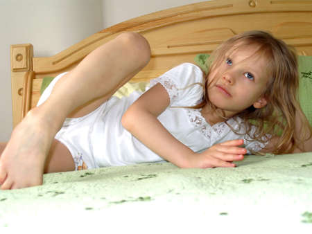 affecting: Morning. Sentimental age. Little girl lying on the bed in the morning