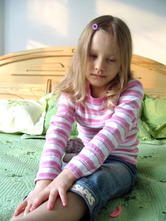 The little girl sitting on the bed. The little girl sitting on the bed, Young girl sitting on a bed, little sad crying girl sitting on the bed. photo