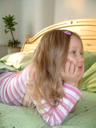 Thinking Girl. Affectionate age. Little girl lying on the bed. photo