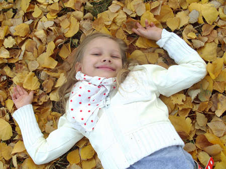 Little girl lying on autumn leaves. photo