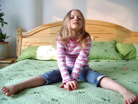 Young girl sitting on a bed Stock Photo - 5951582