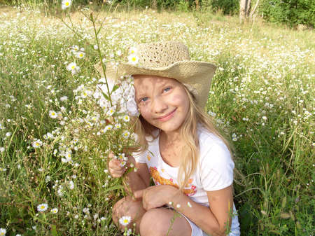 Image of Little girl sitting among wildflowers on the field Little girl in the green field with lots of daisies, wearing a straw hat. Little girl sitting among lots of small wildflowers on the sunny summer field. Little girl admiring the flowers on a dais photo