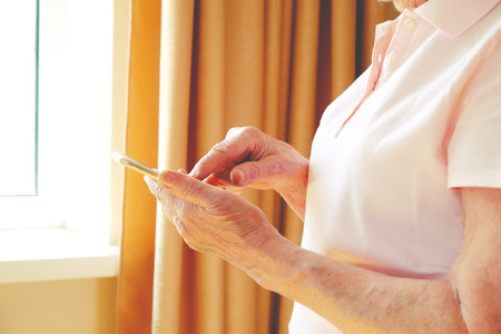 Senior woman sitting on sofa with mobile phone in hand