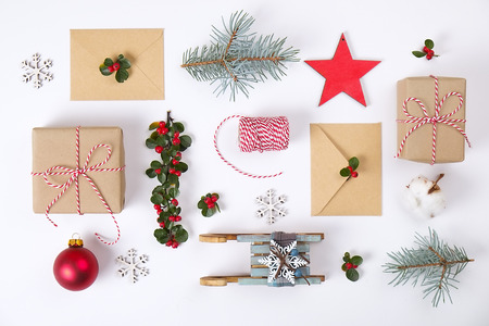 Christmas frame composition. Christmas gift, pine branch, red balls, envelope, white wood snowflakes, ribbon and red berries. Top view, flat lay, copy space Archivio Fotografico