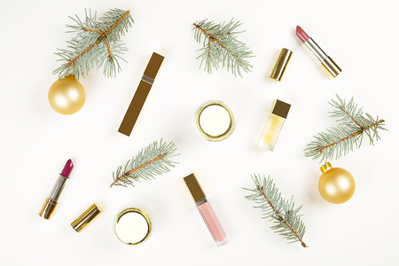 Set of Christmas make up cosmetics products frame with copy space, top view. Makeup products and Christmas decorations on a white background flat lay, text space.