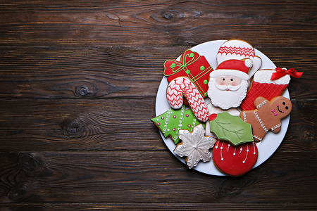 Plate full of tasty Christmas cookies on a brown wooden table