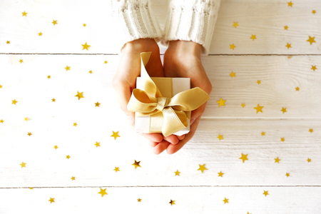 Top view of woman's hands wearing white knitted wool sweater, giving present wrapped in beautiful paper & tied with bow. Holiday greeting concept. Isolated background, copy space, close up, overhead.