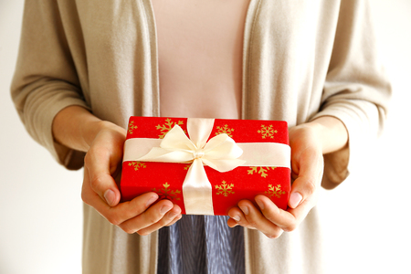 Young casual woman wearing pink shirt and long beige cardigan holding a beautiful present in shiny wrapping tied with golden bow. Giftwrapping concept. Background, copy space, close up.