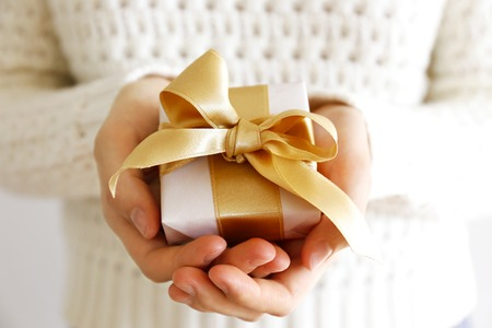 Cropped shot of woman's hands wearing white knitted wool sweater, giving present wrapped Stock Photo