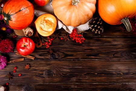 Thanksgiving background concept. Local produce pumpkin, apples & autumn leaves with other fruits, berries & vegetables for decoration on wood textured table. Close up, copy space, top view, flat lay.