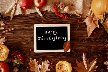 Happy thanksgiving concept. Still life composition with pumpkin and oher fruits and vegetble small decoration with funny font text white text. Wood textured table background. Top view, close up. Stock Photo