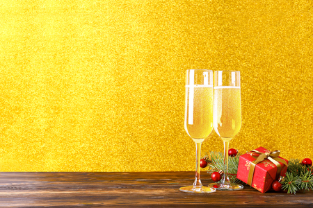Beautiful christmas composition with two glasses of sparkling wine, decorations on wood textured table. New years eve tradition to celebrate with champagne. Close up, copy space, background. Stock Photo