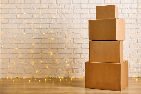 Stack of four blank brown freight boxes, different size, brick wall with Christmas lights on background. Moving company / delivery service holiday deals promotion concept. Copy space, close up.