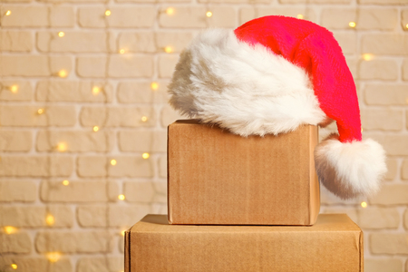 Blank brown freight box with Santa hat on top with Christmas lights on background.