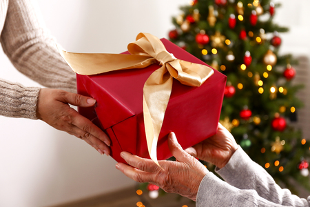 Anciana celebrando la Navidad en casa, con pino de vacaciones decorado en el fondo. Anciana en un hogar de ancianos. De cerca, copie el espacio, foto recortada. Foto de archivo