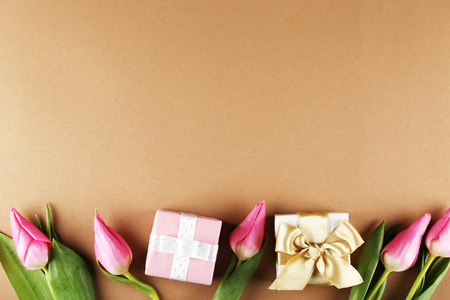 Fresh flower composition, bouquet of bi color pink tulips, brown paper background with present. International Womens day, mothers day greeting concept. Copy space, close up, top view, flat lay.