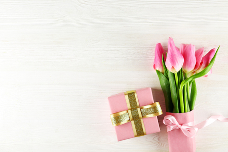 Fresh flower composition, bouquet of bi color pink tulips, white wooden texture table background. International Womens day, mothers day greeting concept. Copy space, close up, top view, flat lay.